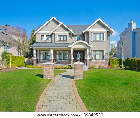 Big custom made luxury house with long doorway and nicely trimmed front yard in the suburbs of Vancouver, Canada. - stock photo