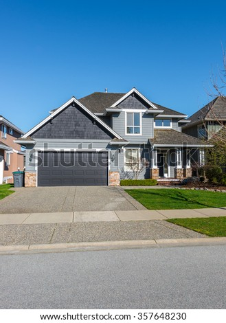 Big custom made luxury house with nicely landscaped and trimmed front yard and driveway to garage in the suburbs of Vancouver, Canada. Vertical.