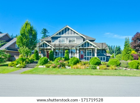 Big custom made luxury house with nicely landscaped and trimmed front yard and long and wide driveway in the suburbs of Vancouver, Canada.