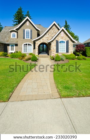 Big custom made luxury house with nicely landscaped and trimmed front yard and paved doorway in the suburbs of Vancouver, Canada. Vertical. - stock photo