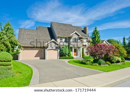 Big custom made luxury house with nicely landscaped front yard and long and wide driveway in the suburbs of Vancouver, Canada. - stock photo