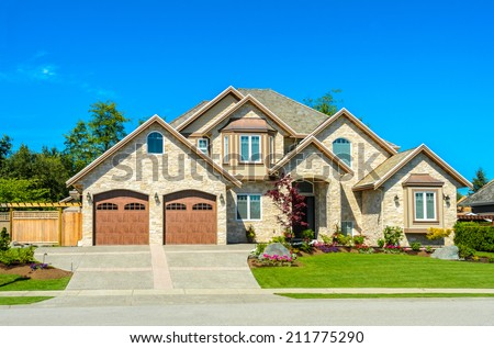 Big custom made luxury house with nicely landscaped front yard and long and wide driveway to garage in the suburbs of Vancouver, Canada. - stock photo