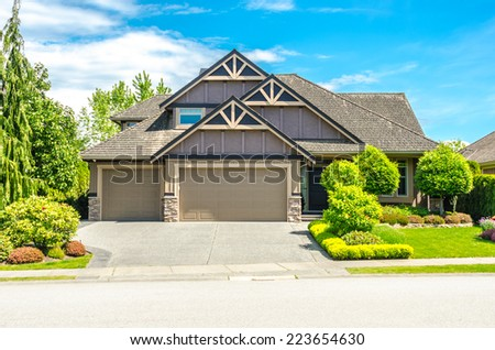 Big custom made luxury house with nicely landscaped front yard and long and wide driveway to garage in the suburb of Vancouver, Canada. - stock photo