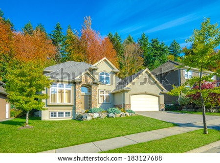 Big custom made luxury house with nicely landscaped front yard and long and wide driveway to the triple doors garage in the suburbs of Vancouver, Canada. - stock photo