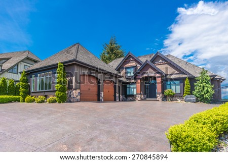 Big custom made luxury house with nicely landscaped front yard and long and wide paved driveway to the triple doors garage in the suburb of Vancouver, Canada. - stock photo