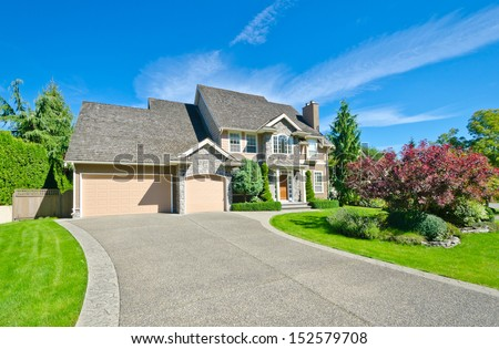 Big custom made luxury house with nicely landscaped front yard and long driveway in the suburbs of Vancouver, Canada. - stock photo