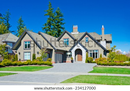 Big custom made luxury house with nicely landscaped front yard, double doors garage and long and wide driveway in the suburbs of Vancouver, Canada. - stock photo