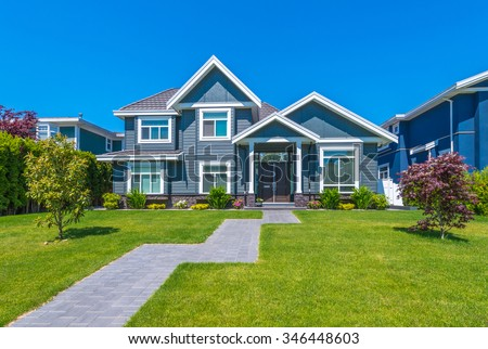 Big custom made luxury house with nicely trimmed and landscaped front yard and long doorway  in the suburb of Vancouver, Canada.
