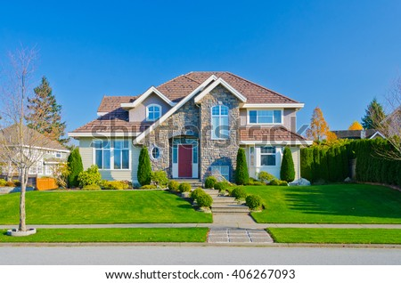 Big custom made luxury house with nicely trimmed and landscaped front yard in the suburb of Vancouver, in colorful fall time. Canada.