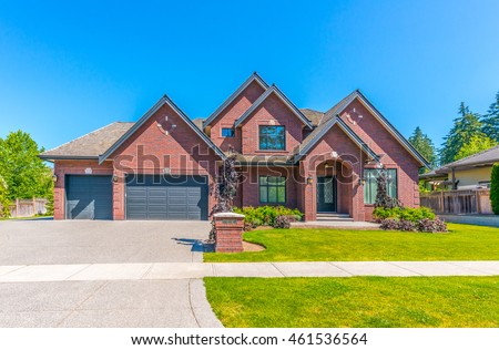 Big custom made luxury house with nicely trimmed and landscaped front yard in the suburbs of Vancouver, Canada.