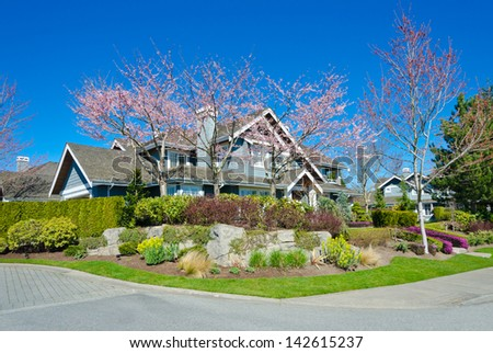 Big custom made luxury house with nicely trimmed and landscaped front yard lawn in the suburbs of Vancouver, Canada.