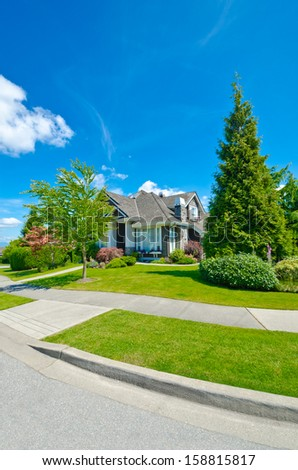 Big custom made luxury house with nicely trimmed and landscaped front yard on the  empty street with pedestrian sidewalk in the suburbs of Vancouver, Canada.