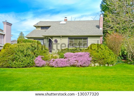 Big custom made luxury house with nicely trimmed front lawn in the suburbs of Vancouver, Canada. - stock photo