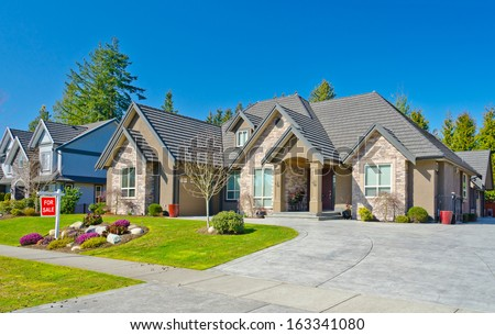 Big custom made luxury house with wide and long driveway and nicely trimmed and landscaped front yard lawn in the suburbs of Vancouver, Canada.