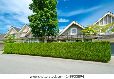 Big custom made luxury houses behind the green nicely trimmed fence in the suburbs of Vancouver, Canada.  Keeps privacy and security. Landscape trimming design. - stock photo