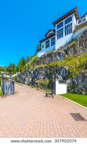 Big custom made luxury modern house on the rock with nicely paved driveway in the suburbs of Vancouver, Canada. Vertical. - stock photo