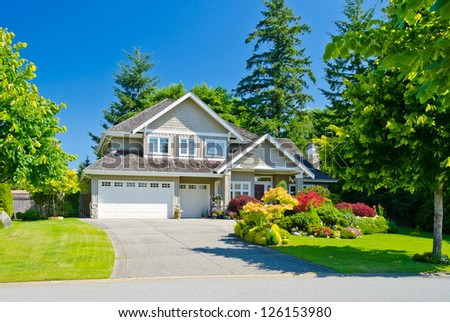 Big custom made triple doors garage luxury house with nicely landscaped front yard in the suburbs of Vancouver, Canada. - stock photo
