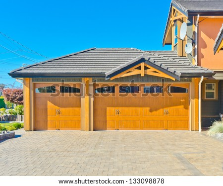 Big custom made triple doors garage with nicely paved driveway, front yard in the suburbs of Vancouver, Canada. - stock photo