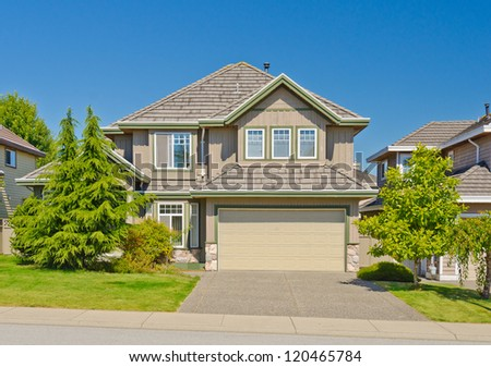 Big custom made with double doors garage luxury house and nicely landscaped front yard in the suburbs of Vancouver, Canada. - stock photo
