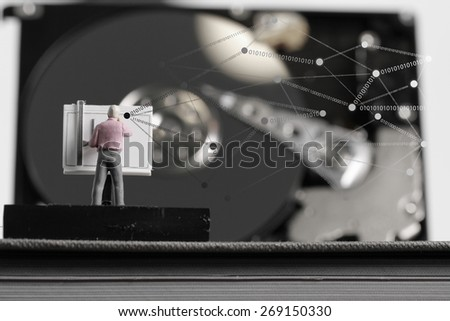 Big data concept-miniature engineer working with drafting table with open hard disk and  social network diagram - stock photo