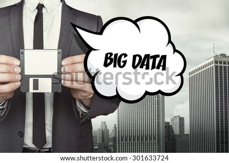 Big data text on speech bubble with businessman holding diskette on cityscape background - stock photo