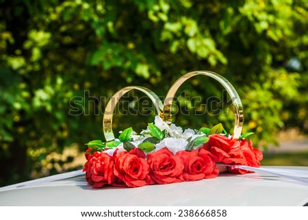 big decorate wedding rings on a roof of the car - stock photo