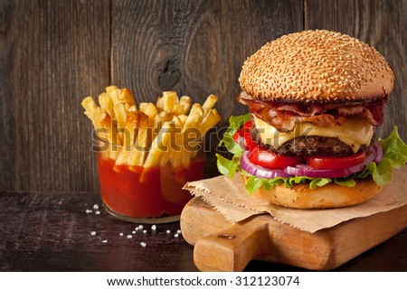 Big delicious cheeseburger stacked high with a bacon, beef patty, cheese, lettuce, red onion and tomato on sesame seed bun served  on wooden cutting board and fried potatoes with sauce. - stock photo