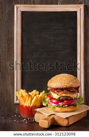 Big delicious cheeseburger stacked high with a bacon, beef patty, cheese, lettuce, red onion and tomato on sesame seed bun served  on wooden cutting board and fried potatoes with sauce.