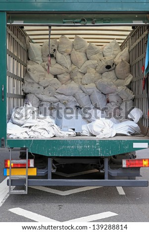 Big delivery truck collecting dirty laundry bags - stock photo