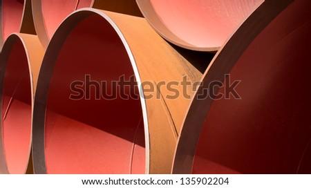 Big diameter stacked red orange pipes - stock photo