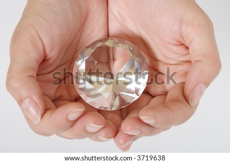 Big diamond in two hands. Isolated on white background. - stock photo