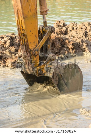 Big digger with brown mud on coastal lake