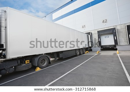 Big distribution warehouse with gates for loads and truck - stock photo