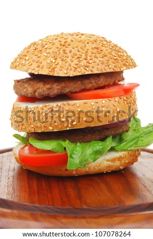 big double grilled hamburger on wooden plate isolated  over white background - stock photo