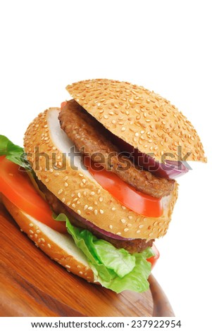 big double grilled hamburger on wooden plate isolated  over white background