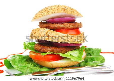 big double hamburger on ceramic plate with cutlery isolated  over white background - stock photo