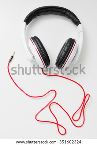 Big earphones for dj on a light table with red cable. Musical concept - stock photo