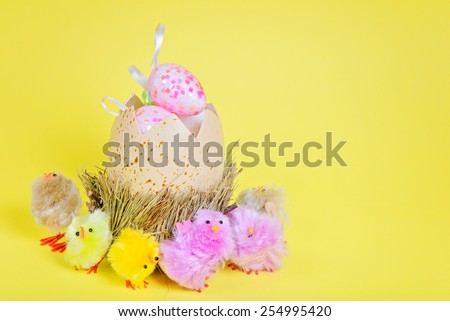 Big easter egg and chickens over yellow paper - stock photo