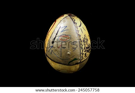 Big egg with with cryptic information written on it, isolated on black.