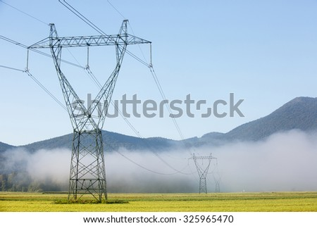 Big electricity high voltage pylons with power lines on a green field in a foggy morning. Sustainable resources, green energy, energy and power industry concept.  - stock photo