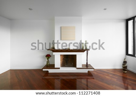 Big empty living room with a chimney, white wall and wooden floor - stock photo