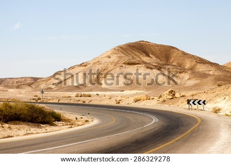 Big empty road with left turn in a mountains - stock photo