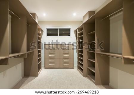 Big empty walk in wardrobe in luxurious house - stock photo
