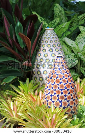 Big enameled vase with pretty flower patterns decorating the garden, surrounded by Bromeliad plant