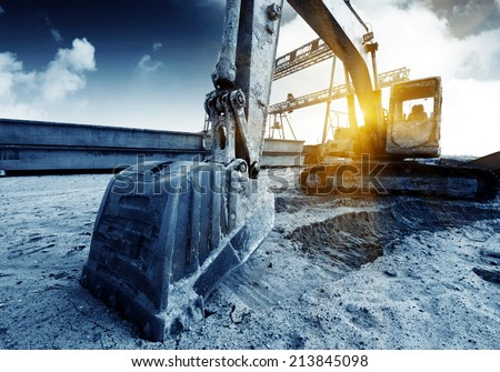 Big excavator on new construction site, in the background the blue sky and sun