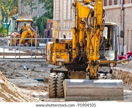 Big excavators at urban construction site - stock photo