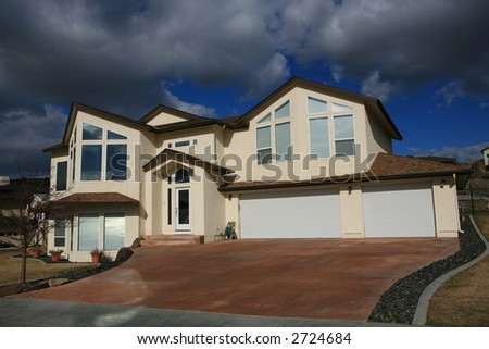 Big expensive modern house on a hill with big windows and puffy white clouds - stock photo