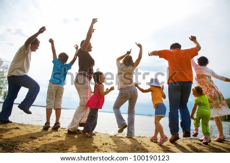 Big family from  adults and children dancing on the beach