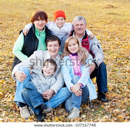 Big family in autumn park. Mother, father, grandmother, grandfather and children outdoors - stock photo