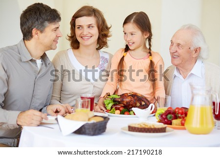 Big family looking at young man during traditional Thanksgiving dinner - stock photo